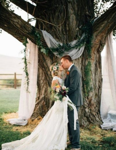 a-tree-with-airy-fabric-and-a-greenery-garland-as-a-ceremony-backdrop-480x720